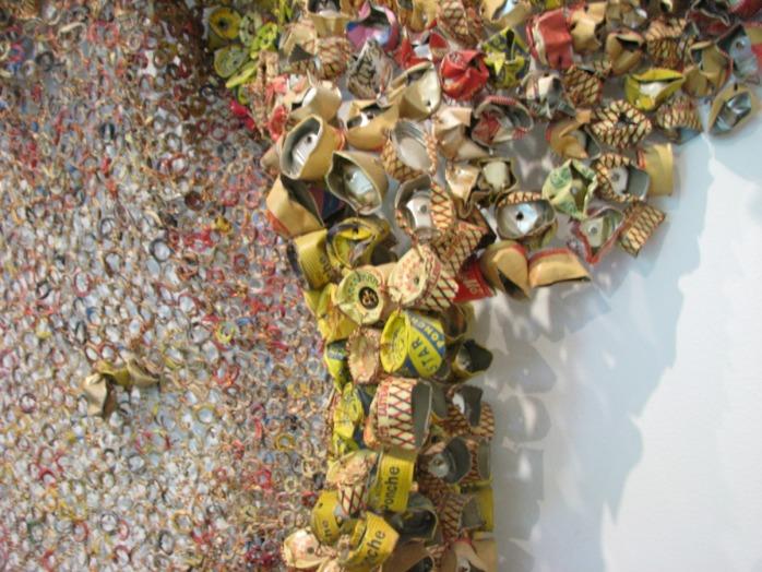 A obra, que lembra um trabalho de tapeçaria, é composta de milhares de tampas de alumínio e selos de bebidas alcoólicas.