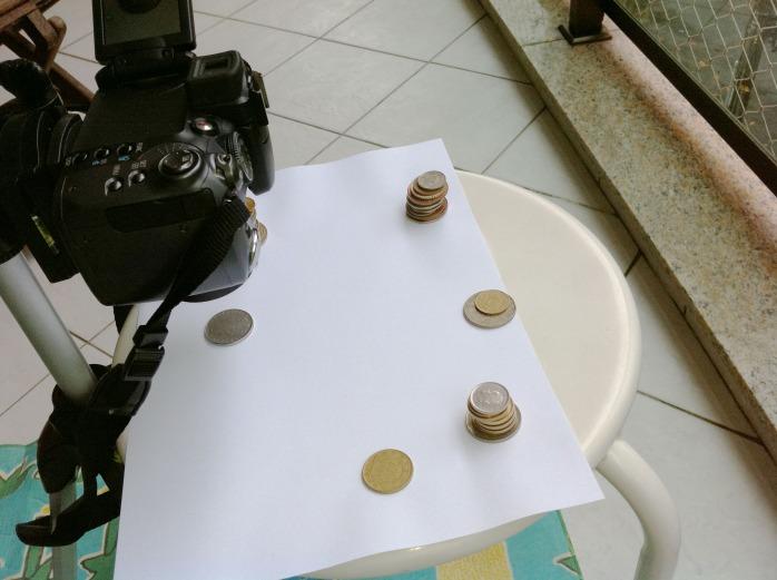 Tripé com câmera e banco sobre o qual estão as peças a serem fotografadas. Neste caso, algumas moedas da minha coleção.